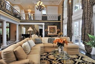 Traditional Great Room with Chandelier, High ceiling, interior wallpaper, stone tile floors, Loft, Crown molding, Columns