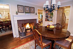 Country Dining Room with Crown molding, Chandelier, Built-in bookshelf, Hardwood floors, Fireplace, Standard height