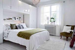 Contemporary Guest Bedroom with Chandelier, Built-in bookshelf, flush light, Hardwood floors