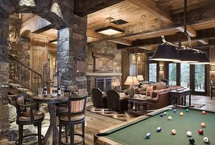 Rustic Basement with Pendant light, French doors, Rustic wood bar table, Exposed beam, stone fireplace, flush light