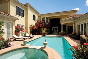 Mediterranean Swimming Pool with French doors, exterior stone floors, Pool with hot tub