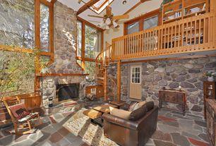 Rustic Living Room with slate floors, Ceiling fan, Glass panel door, Loft, Skylight, stone fireplace, High ceiling