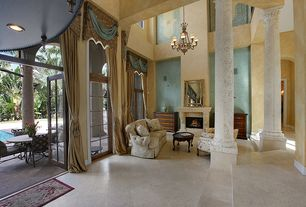 Traditional Living Room with Chandelier, Fireplace, Transom window, simple granite floors, Columns, French doors