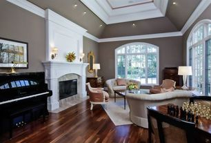 Traditional Living Room with stone fireplace, Wall sconce, High ceiling, Arched window, can lights, Hardwood floors
