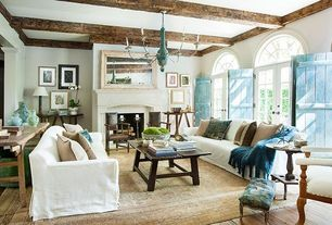 Cottage Living Room with Exposed beam, Chandelier, Transom window, French doors, Cement fireplace, Arched window