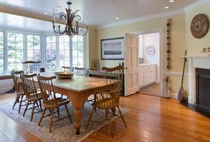 Country Dining Room with Hardwood floors, Crown molding, Chandelier, Cement fireplace