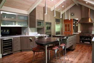 Contemporary Kitchen with Simple marble counters, Flat panel cabinets, Kitchen island, Wine refrigerator, Pendant light