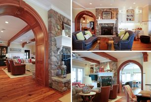 Traditional Living Room with Exposed beam, Wainscotting, stone fireplace, Pine flooring, Crown molding, Arched doorway