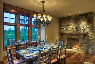 Rustic Dining Room with Chandelier, picture window, can lights, Standard height, Fireplace, stone fireplace, Hardwood floors