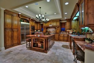 Mediterranean Kitchen with Undermount sink, double wall oven, Crown molding, Built In Refrigerator, stone tile floors, Paint