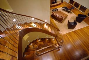 Contemporary Staircase with curved staircase, Built-in bookshelf, can lights, Hardwood floors, Cathedral ceiling