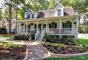 Traditional Exterior of Home with Covered front porch, Fence, French doors, Bird bath, Pathway, Raised beds