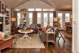 Cottage Living Room with Transom window, French doors, stone fireplace, Built-in bookshelf, Hardwood floors