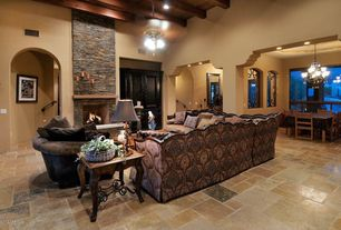 Mediterranean Living Room with High ceiling, Ceiling fan, Exposed beam, limestone tile floors, stone fireplace