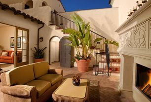 Mediterranean Patio with Outdoor fireplace, Deck Railing, Paint 1, Outdoor wicker furniture, Spanish tile roof, French doors