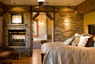 Rustic Master Bedroom with Wall sconce, can lights, Wood bedframe, Fireplace, insert fireplace, Exposed beam, Ceiling fan