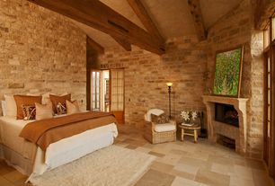 Mediterranean Master Bedroom with Transom window, High ceiling, limestone floors, Exposed beam, stone fireplace, French doors