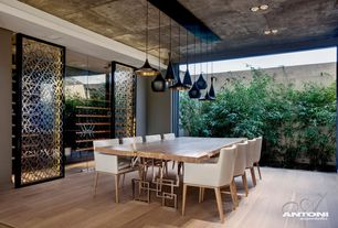 Modern Dining Room with specialty door, Glazed porcelain floor tile, Pendant light, Hardwood floors