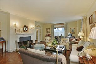 Traditional Living Room with Hardwood floors, Arched window, Cement fireplace, Crown molding, Wall sconce, French doors