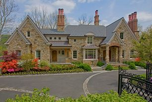 Traditional Exterior of Home with Arched window, Wrought iron gate, Chimney, Bird bath, Casement, Arched door