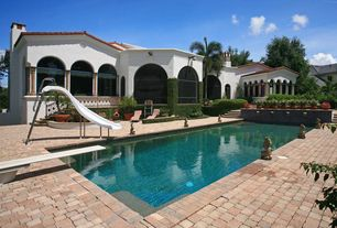 Mediterranean Swimming Pool with Lap pool, exterior stone floors, Raised beds, Arched window, Pathway