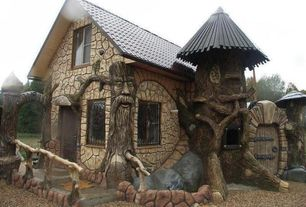 Eclectic Exterior of Home with Arbor, Raised beds, Tree house inspired home, Pathway, Barn door, Gate