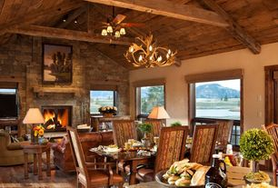 Rustic Great Room with flush light, stone fireplace, French doors, Chandelier, Exposed beam, Hardwood floors, Ceiling fan