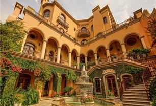 Mediterranean Exterior of Home with Metal stair railing, Water feature, Arched window, Arched doorway