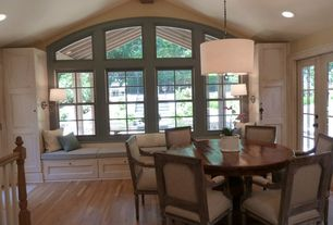 Traditional Dining Room with Arched window, Hardwood floors, Window seat, French doors, Built-in bookshelf, Wall sconce