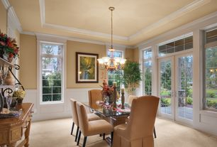Traditional Dining Room with French doors, Wainscotting, Carpet, Chandelier, Crown molding, Transom window