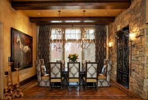 Mediterranean Dining Room with Wall sconce, terracotta tile floors, Standard height, Casement, Exposed beam, can lights