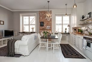 Traditional Great Room with interior brick, Chandelier, Crown molding, sandstone floors, Pendant light, Built-in bookshelf