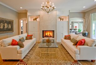 Traditional Living Room with Built-in bookshelf, Hardwood floors, Chandelier, stone fireplace, Crown molding