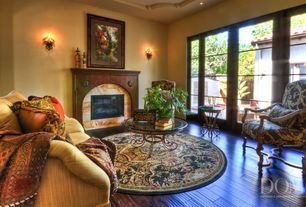 Mediterranean Living Room with stone fireplace, Wall sconce, French doors, High ceiling, Hardwood floors