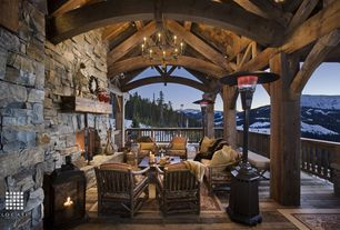 Country Porch with Exterior stone siding, Deck Railing, Exposed beam ceiling, Outdoor chandelier, Wrap around porch