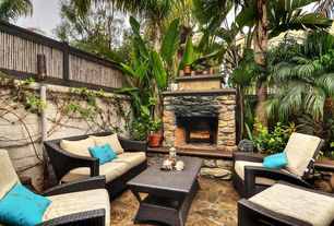 Tropical Patio with exterior stone floors, outdoor pizza oven, Fence