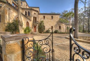 Mediterranean Front of Home with Natural stone facade - exterior house, Stone and brick driveway, Entry gate - bronze