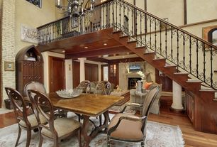 Mediterranean Dining Room with Cathedral ceiling, Hardwood floors, interior brick, Chandelier, Loft