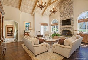 Traditional Living Room with Virginia mill works golden teak acacia handscraped, Arched window, stone fireplace, Chandelier