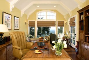 Traditional Home Office with Wall sconce, Arched window, can lights, Standard height, Built-in bookshelf, Hardwood floors