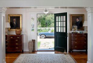 Traditional Entryway with Glass panel door, Built-in bookshelf, Hardwood floors, Pendant light