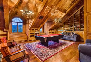 Rustic Game Room with Cathedral ceiling, Hardwood floors, Exposed beam, Built-in bookshelf, Chandelier, Arched window