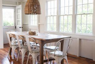 Cottage Dining Room with Emac Lawton Wicker Pendant Light: wicker bell, Wainscotting, Glass panel door, Hardwood floors