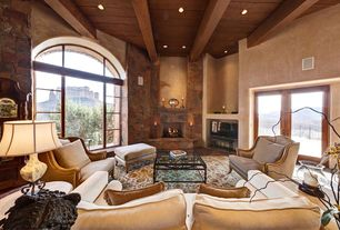 Mediterranean Living Room with Wood ceiling, stone fireplace, Stacked stone wall, Spanish colonial, Exposed beam, Area rug