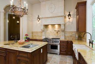 Mediterranean Kitchen with Chandelier, limestone tile floors, Pendant light, Custom hood, Framed Partial Panel, Stone Tile