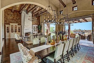 "Mediterranean Great Room with Currey and company fitzjames 25"" wide lantern chandelier, Cement fireplace, can lights, Columns"