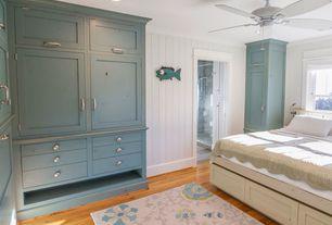 Cottage Master Bedroom with Hardwood floors, Wall paneling, Area rug, Under bed storage, Ceiling fan, Built-in bookshelf