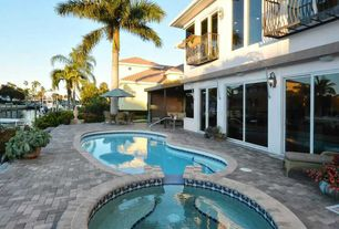 Tropical Swimming Pool with Raised beds, exterior stone floors, Pool with hot tub