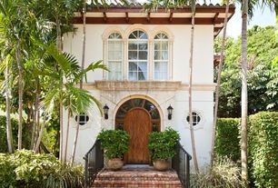 Mediterranean Exterior of Home with Arched window, exterior brick floors, Fence