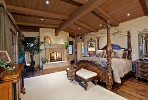 Mediterranean Master Bedroom with Exposed beam, metal fireplace, Hardwood floors, stone fireplace, Fireplace, can lights